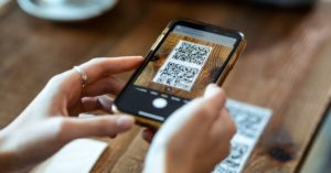someone using their mobile device to scan a qr code on a table